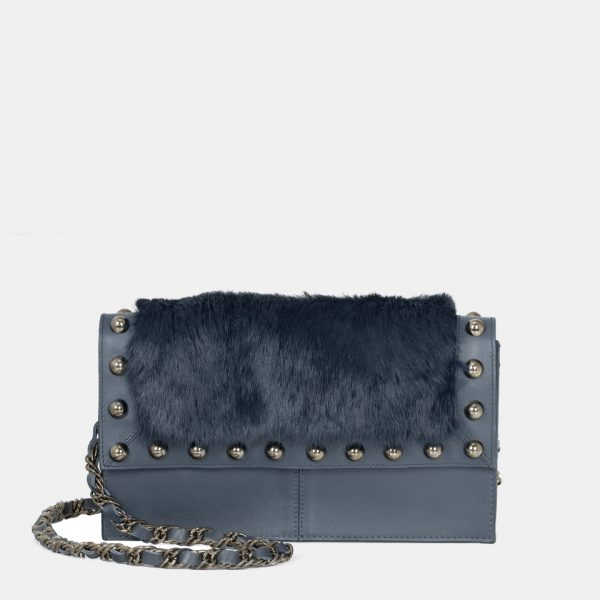 Sus detalles dorados contrastan con el azul de este bolso de piel y pelo natural.